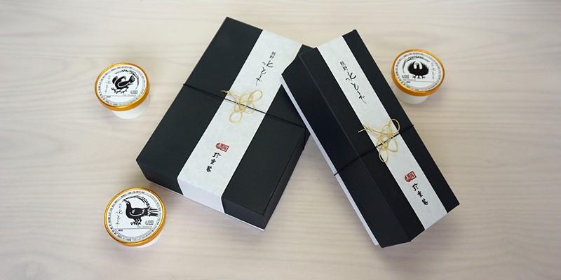 熊野本宮大社・熊野速玉大社・熊野那智大社の熊野三山と関係深い八咫烏(ヤタガラス)をモチーフ。その八咫烏デザインの容器を、金の水引飾りをあしらった贈答用ケースに詰め合わせました。