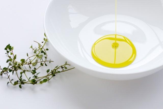 白い丸皿にオリーブオイルを垂らしている写真