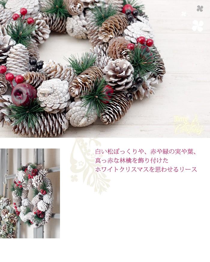 白い松ぼっくりや、赤や緑の実や葉、真っ赤な林檎を飾り付けたホワイトクリスマスを思わせるリース