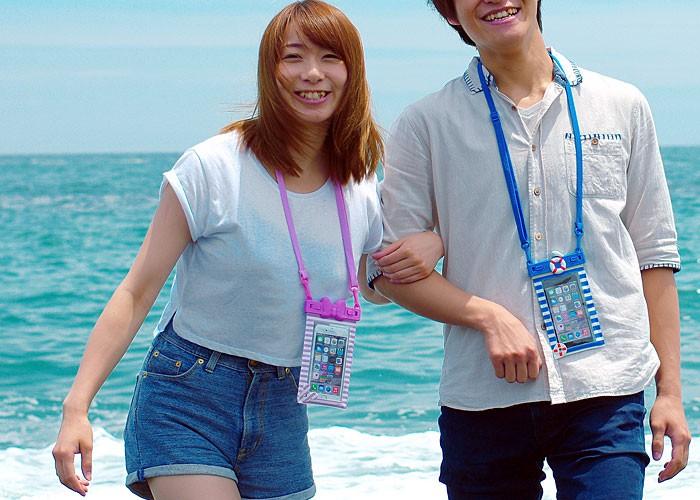 男性と女性が防水ケースを付けて遊んでいる画像