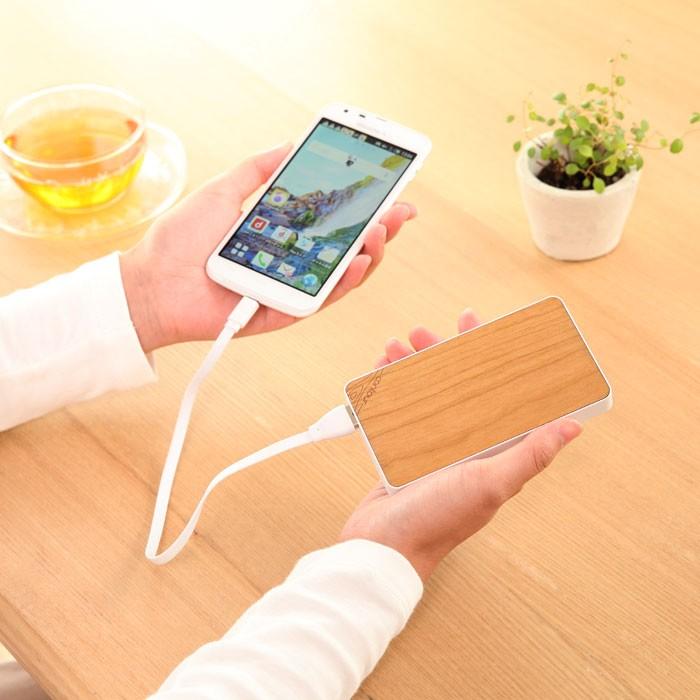 女性がチェリーウッドの充電器でスマートフォンを充電している画像。