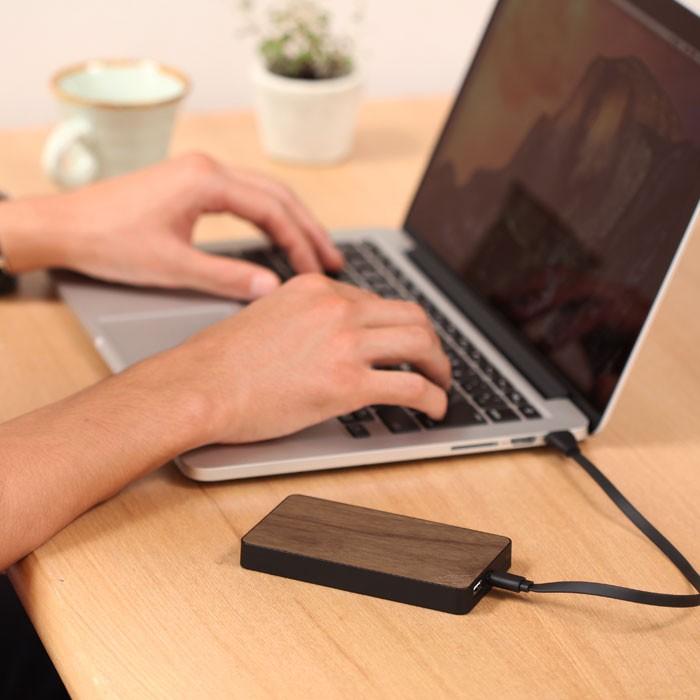 男性がウォルナットの充電器をパソコンで充電している画像。