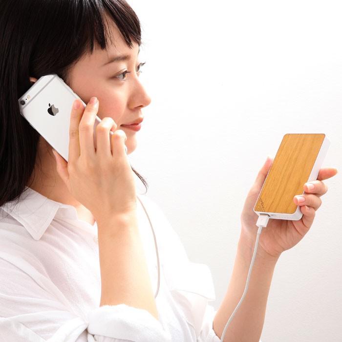 女性がチェリーウッドの充電器でiPhoneを充電しながら通話をしている画像。