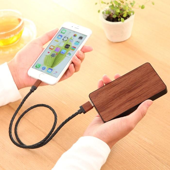 女性がローズウッドのケーブルと充電器を持ってiPhoneを充電している画像。