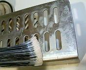 【2】スプレー後ハケで塗り広げ、2〜3分待ってこすってみると、汚れが分解(白く濁っています)され始めました。
